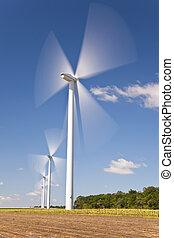 Green Energy Wind Turbines In Field of Sunflowers - A farm...