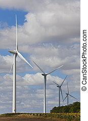 Green Energy Wind Turbines In Field of Sunflowers