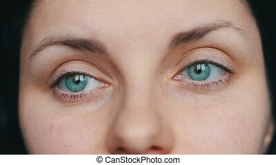 Green-eyed female face looks away and up to the camera. close-up view with sad girl
