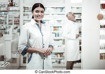 Green-eyed pharmacist. Appealing green-eyed pharmacist smiling broadly while meeting clients in drugstore