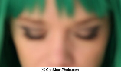 Green-eyed woman wearing a green wig