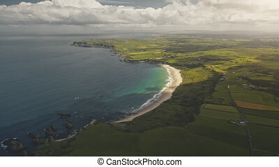 Green farmland at sun ocean bay aerial. Nobody nature landscape. Yellow fields, greenery meadows at summer day. Calm ocean seascape. Rural meadows and lands. Northern Ireland, United Kingdom, Europe