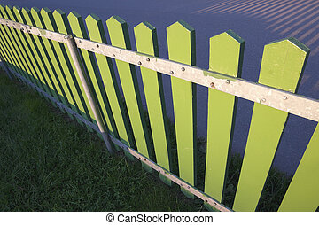 A green wooden fence in the evening sunlight.