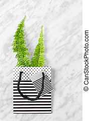Green fern branches in a gift bag on marble background