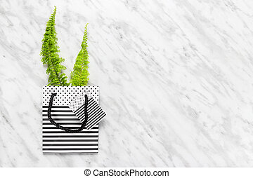 Green fern in a striped gift bag on marble background