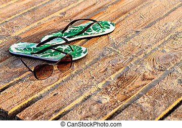 Green flip flops and sunglasses on the wooden boards