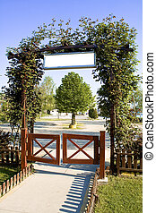 Green floral arch gate over blue sky