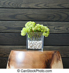 Green flower in vase with wall background.