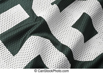 Close up shot of green textured football jersey with partial number
