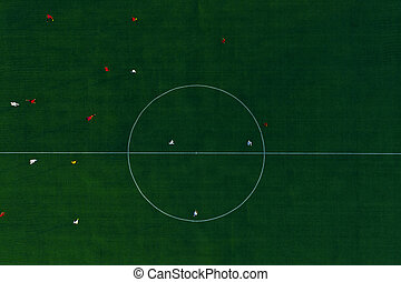 Green football stadium field. Aerial top view. Soccer players