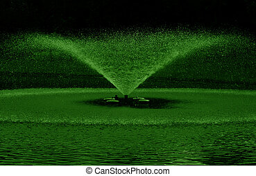 green fountain water in black background