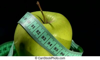 Green, fresh apple with measuring tape on black, rotation, reflection, close up