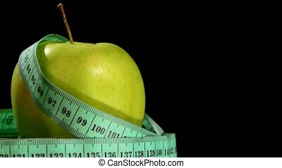 Green, fresh apple with measuring tape on black, rotation, reflection