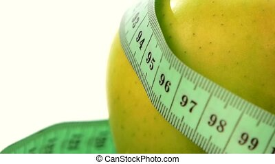 Green, fresh apple with measuring tape on white, rotation, close up