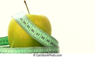 Green, fresh apple with measuring tape on white, rotation