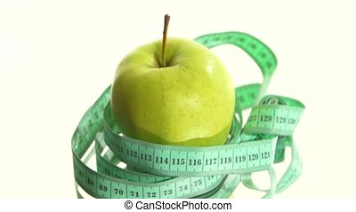 Green, fresh apple with measuring tape on white, rotation, reflection
