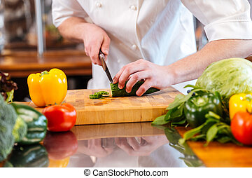 Green fresh cucumber cut by hands of professional chef cook...