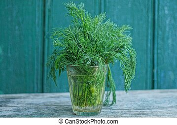green fresh dill in a glass stands on a gray table