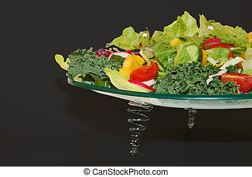 Green garden vegetables on glass plate with black background .
