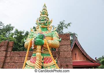 Green giant statue standing front of wall and temple background