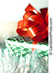 Green gift box with a red ribbon on background close-up