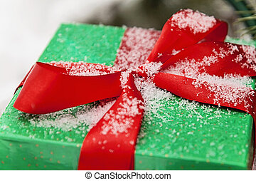 Green gift box with a red ribbon sprinkled with snow close-up