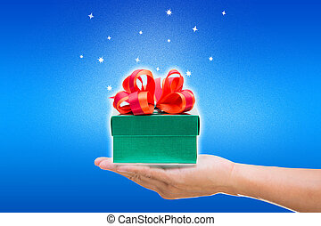 Green gift box with hand on blue background