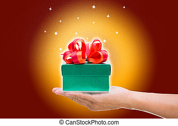 Green gift box with red bow on yellow and brown background