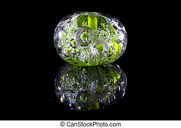 Green glass bead with bubbles on black background