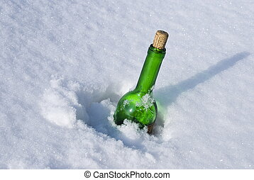 Green glass bottle in the snow