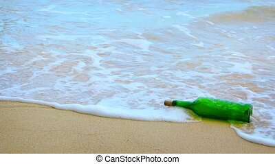 Video UltraHD - Green glass wine bottle rolls playfully in the gentle waves on a sandy tropical beach, with sound.
