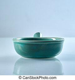 Green glazed ceramic ramekin with handle isolated on grey...