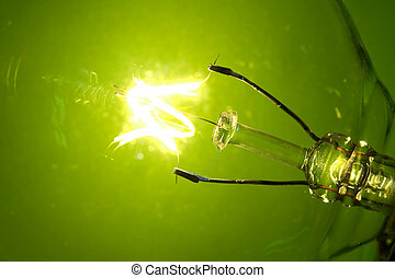 Macro light bulb glowing on a green background