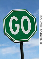 Green Go Sign against blue sky.