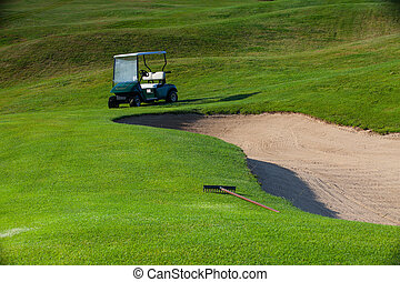 Green golf cart on the empty golf course