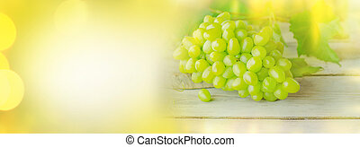 Green grape on blurred golden background