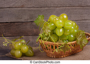 green grapes in a wicker basket on wooden table