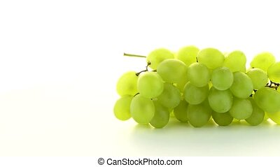 Green grapes rotating on white background.