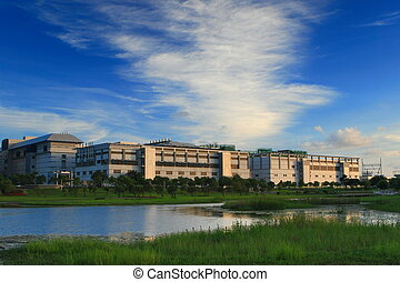 green grass and lake with high technology factory shot in...