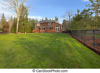 Green grass and large yard with cedar wood house