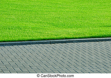 Green grass and pedestrian walkway in the park.