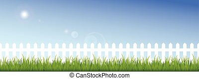 Green grass and white fence on a clear blue sky background