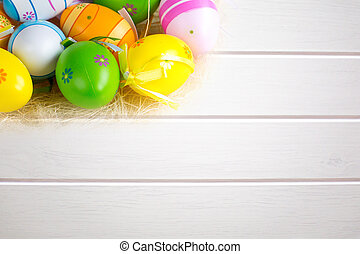 Green grass box with Easter eggs on white wooden board background