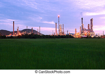 green grass field with scenic of petrochemical oil refinery plant shines at night