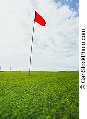 green grass of golf course and red pin flag