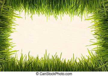green grass on a beige wooden texture