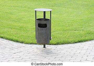Green grass, refuse bin