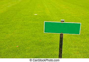 Green grass with a sign, horizontal shot