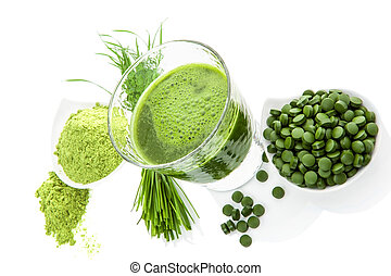 Natural superfood. Alternative medicine. Detox. Ground wheatgrass, barley grass blades, chlorella pills and spirulina green juice isolated on white background. Healthy living.