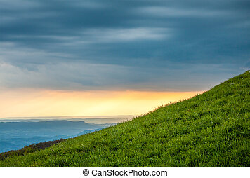 Green hill at beautiful sunset in mountains
